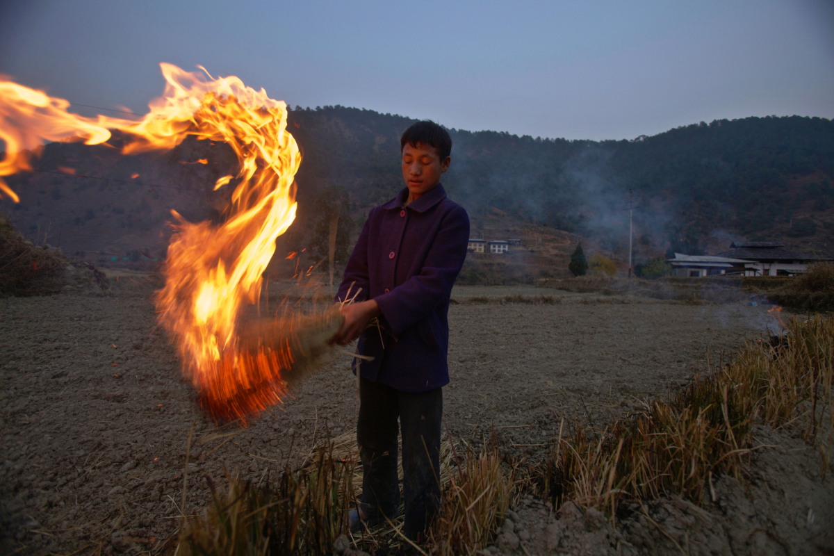 A boy burns rice husk as he works in a field in Punakha. Agriculture in Bhutan has a dominant role in the economy of the coun