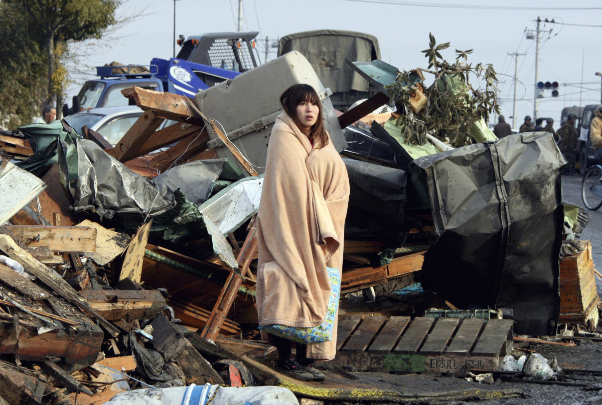 This file photo taken on March 13, 2011 shows Yuko Sugimoto wrapped in a blanket standing as she looks at tsunami damage in t