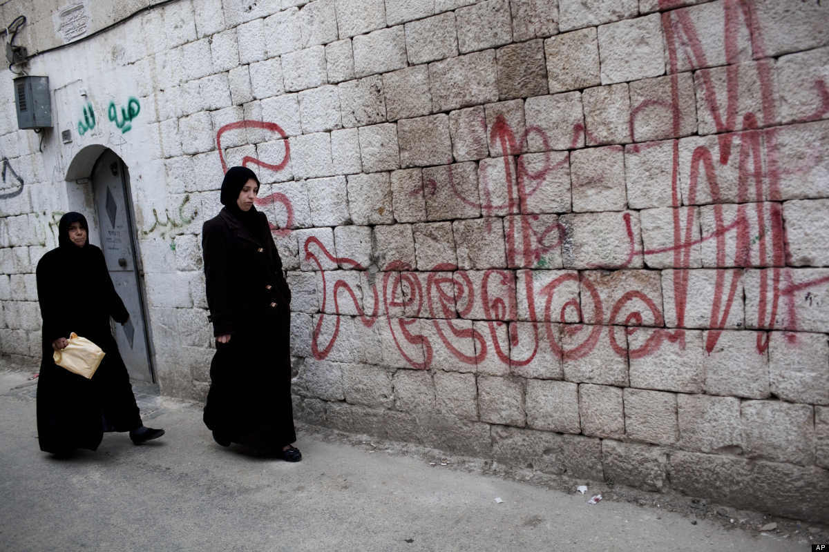 """In this Sunday, March 11, 2012 photo, two Syrian women walk past graffiti that reads """"freedom,"""" during fighting between Syria"""