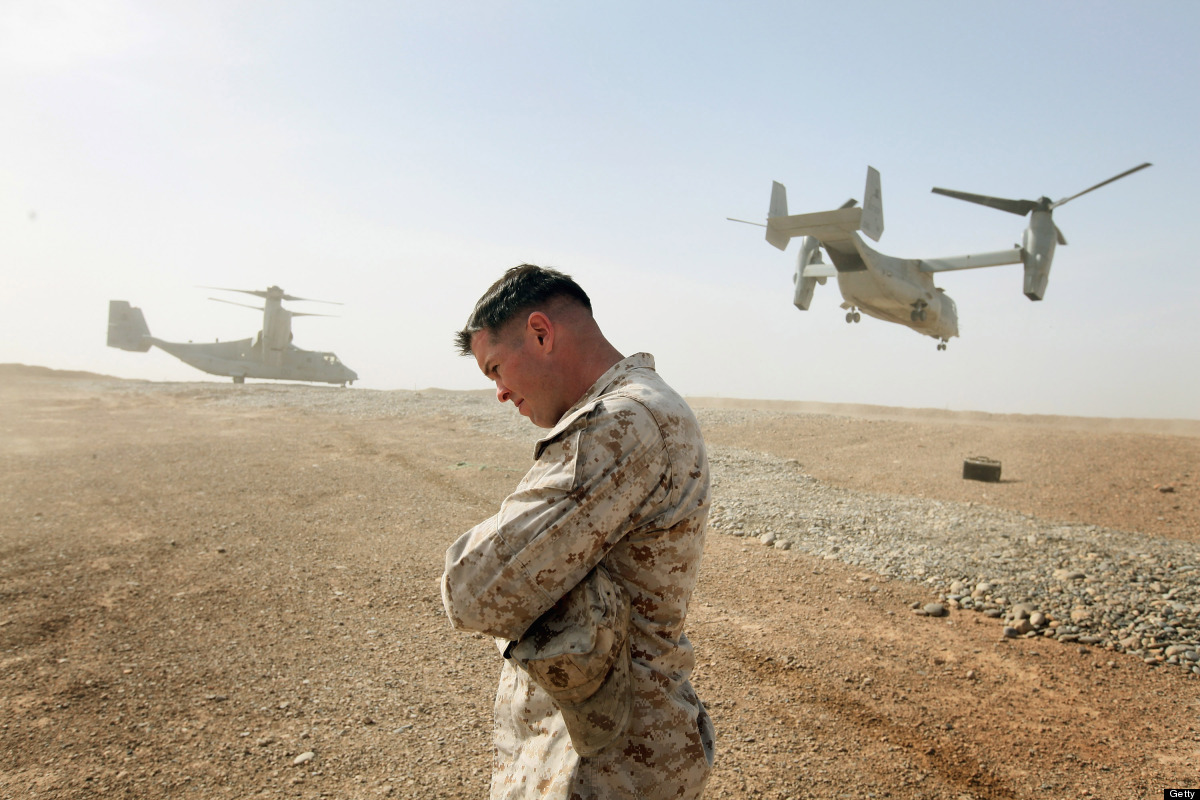 FOB SHUKVANI, AFGHANISTAN - MARCH 14:  Maj. Matt O'Donnell of Glenelg, MD shields himself from rotor wash as Ospreys carrying