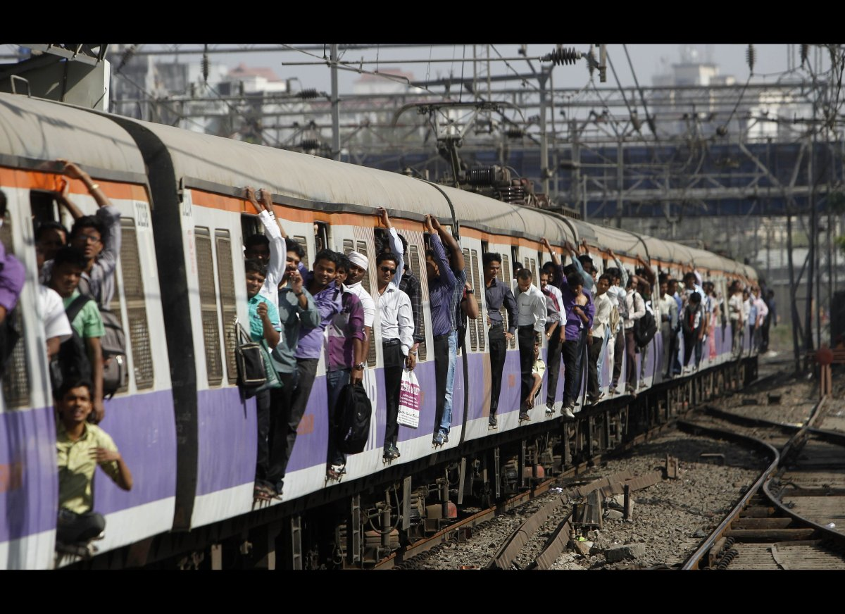 Indian commuters ride in the doorway on a local train in Mumbai, India, on March 14, 2012. The Indian Railway Minister unveil