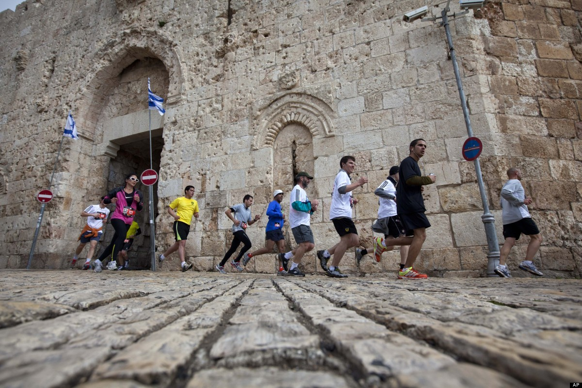 Runners are seen next the Jerusalem's old city Zion Gate during the second annual marathon in Jerusalem, Friday, March 16, 20