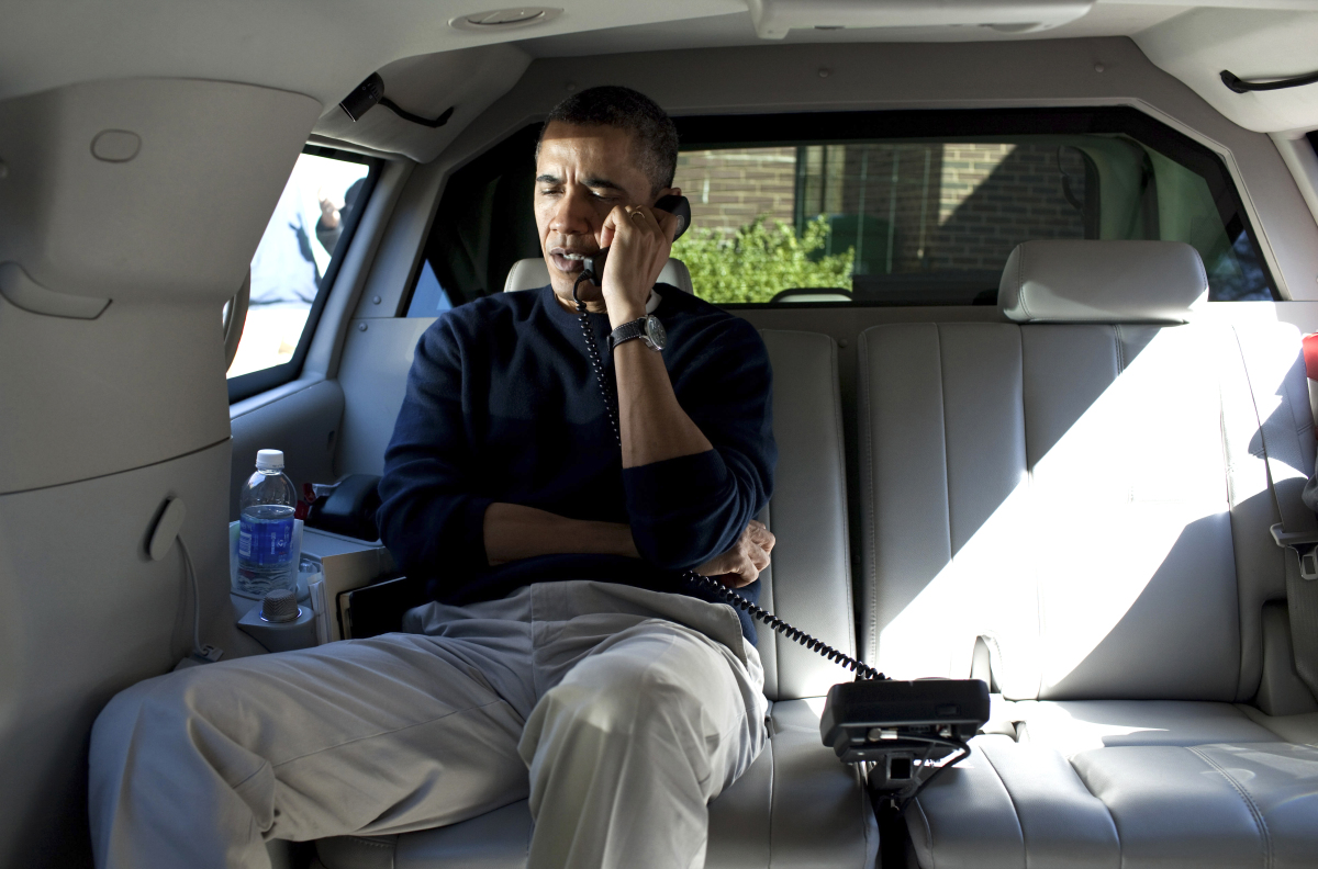 President Barack Obama talks on the phone with Afghanistan President Hamid Karzai from his vehicle outside the Jane E. Lawton