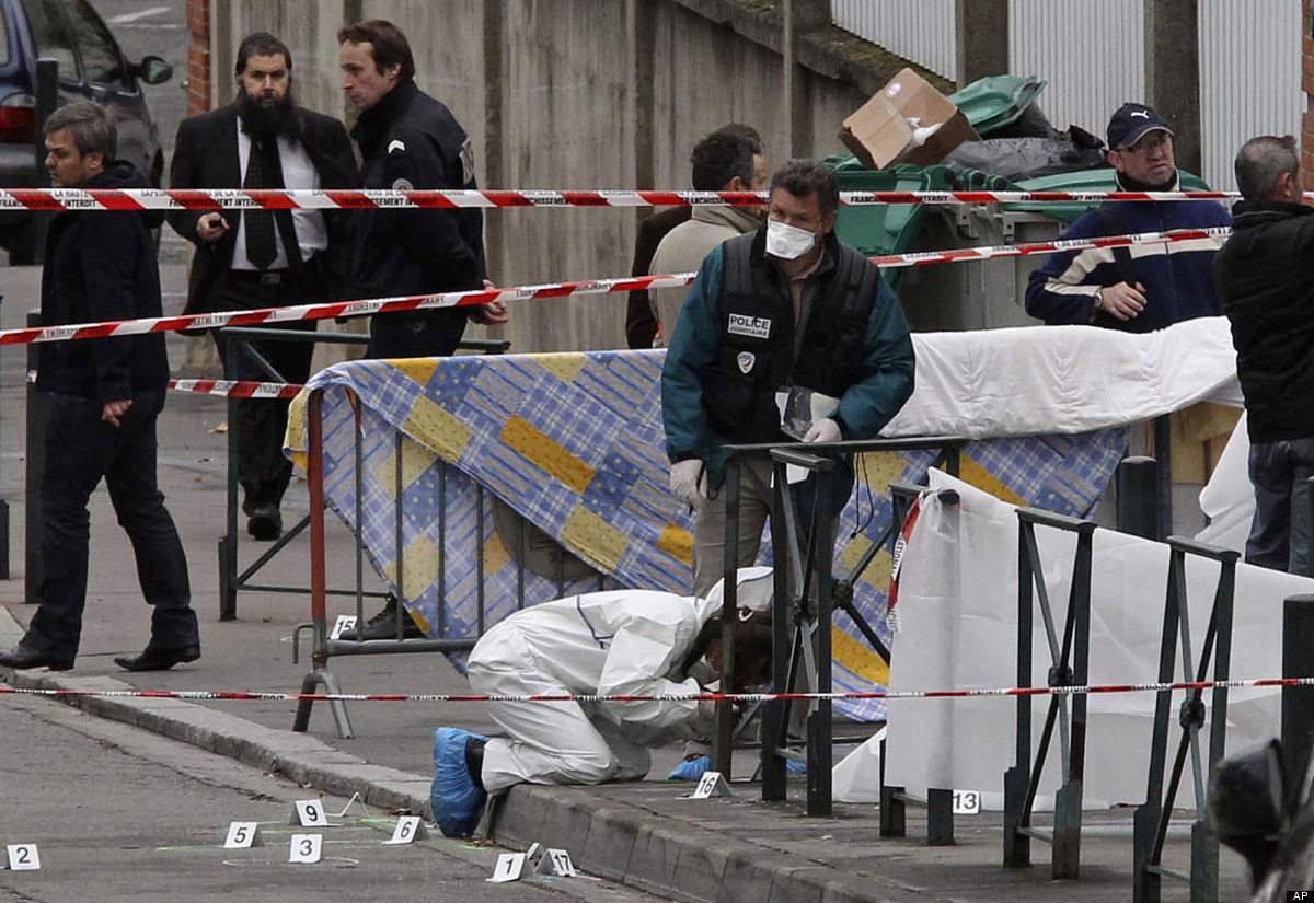 Police officers gather at the site of a shooting in Toulouse, southwestern France, Monday, March 19, 2012. A father and his t