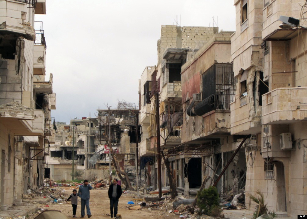 In this March 29, 2012 photo, Syrians walk between destroyed buildings in the Inshaat neighborhood of Homs, Syria. (AP Photo)