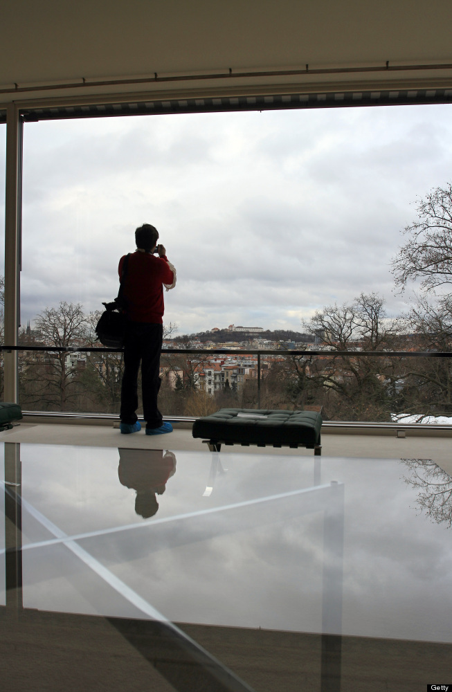 """A man takes pictures trough the restored <a href=""""http://www.tugendhat.eu/en/"""" target=""""_hplink"""">Tugendhat Villa</a>'s living"""