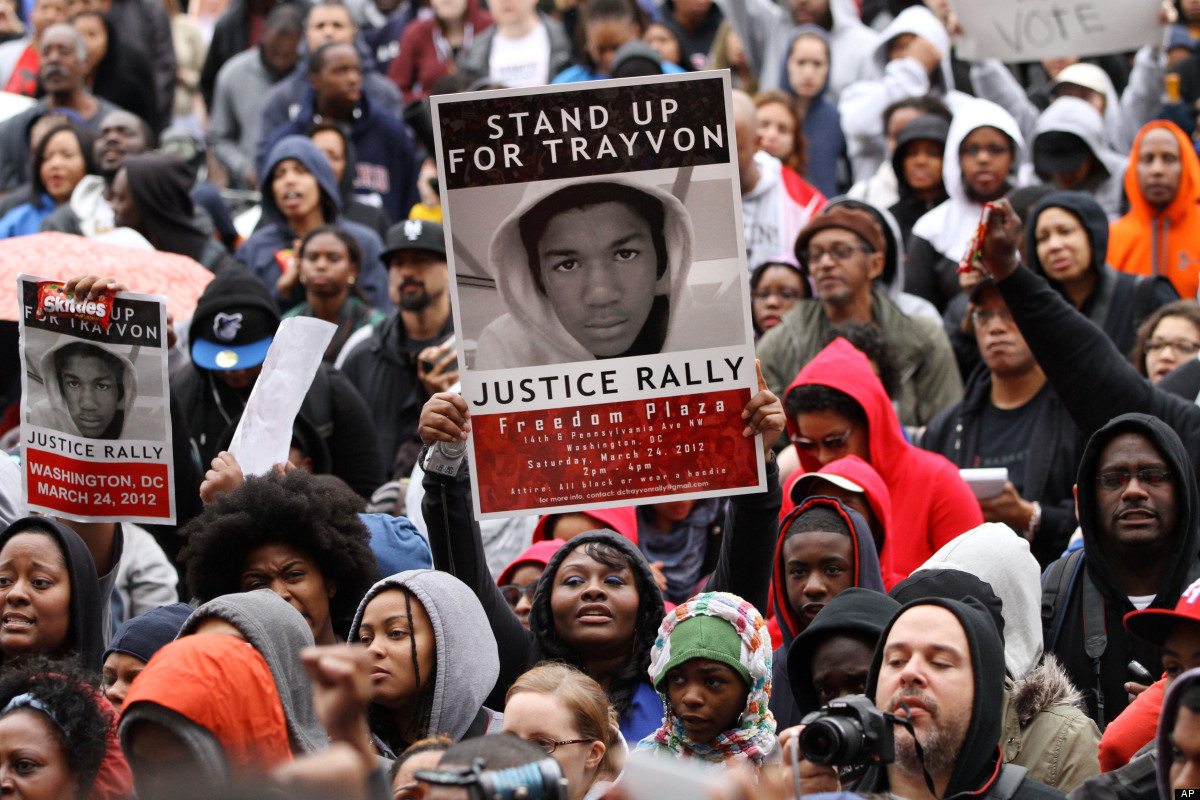 People hold up signs and bags of Skittles candy during a rally in support of Trayvon Martin on Pennsylvania Avenue on Saturda
