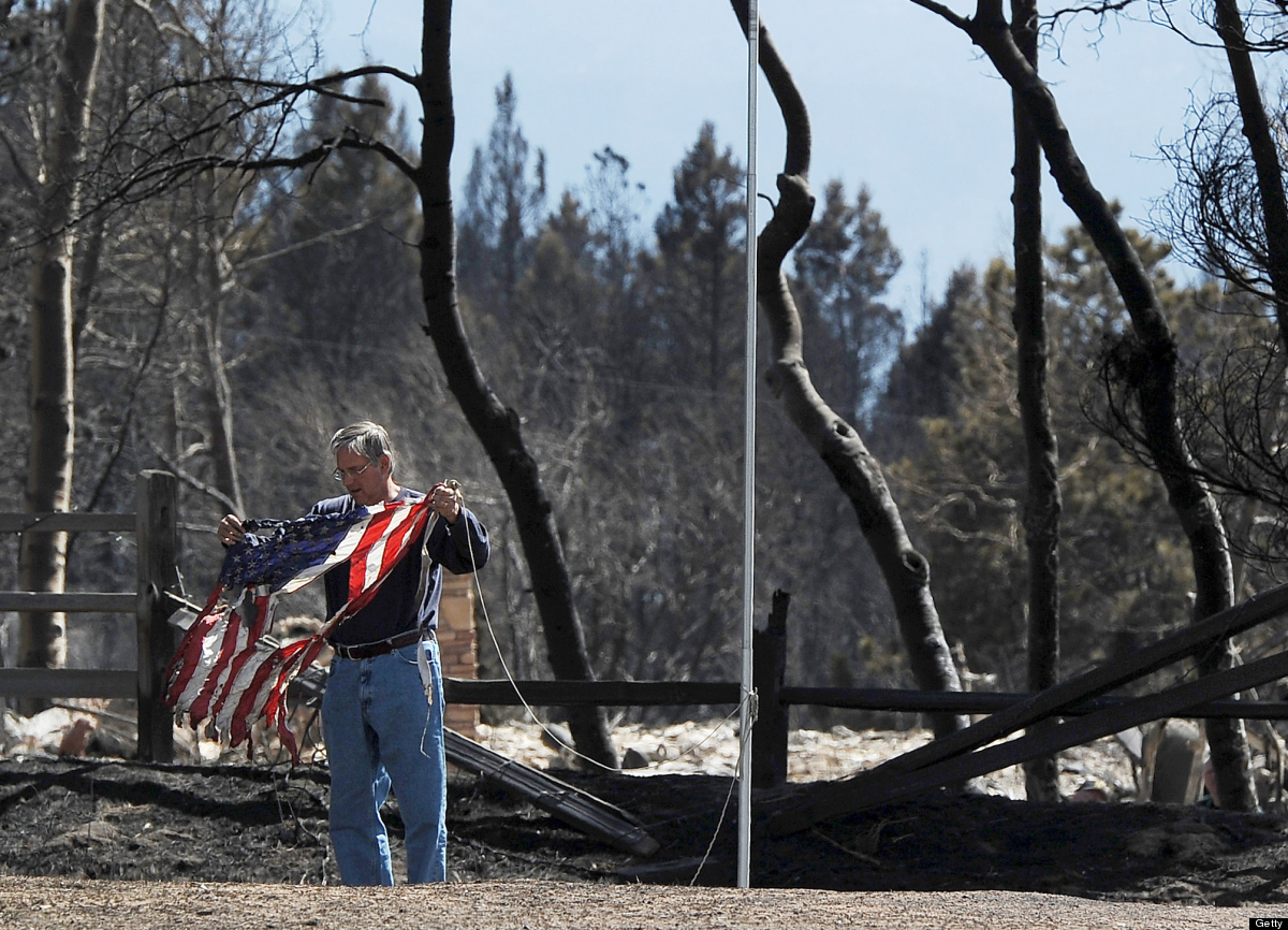 DENVER, CO - MARCH 28:  A man saves a scorched flag from a home destroyed by the Lower North Fork Fire March 28, 2012 in Coni