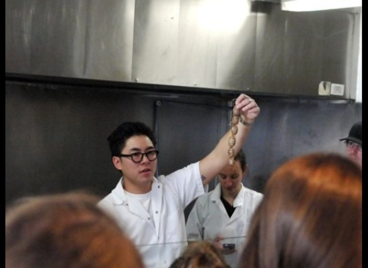 Chef Kris shows the students a strand of Isan sour sausage. Sqirl Preserves' very own Jessica Koslow can be seen texting in t