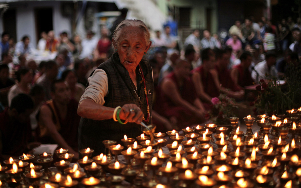An elderly exiled Tibetan lights lamps during a special prayer session for Tibetan Jampa Yeshi who immolated himself Monday d