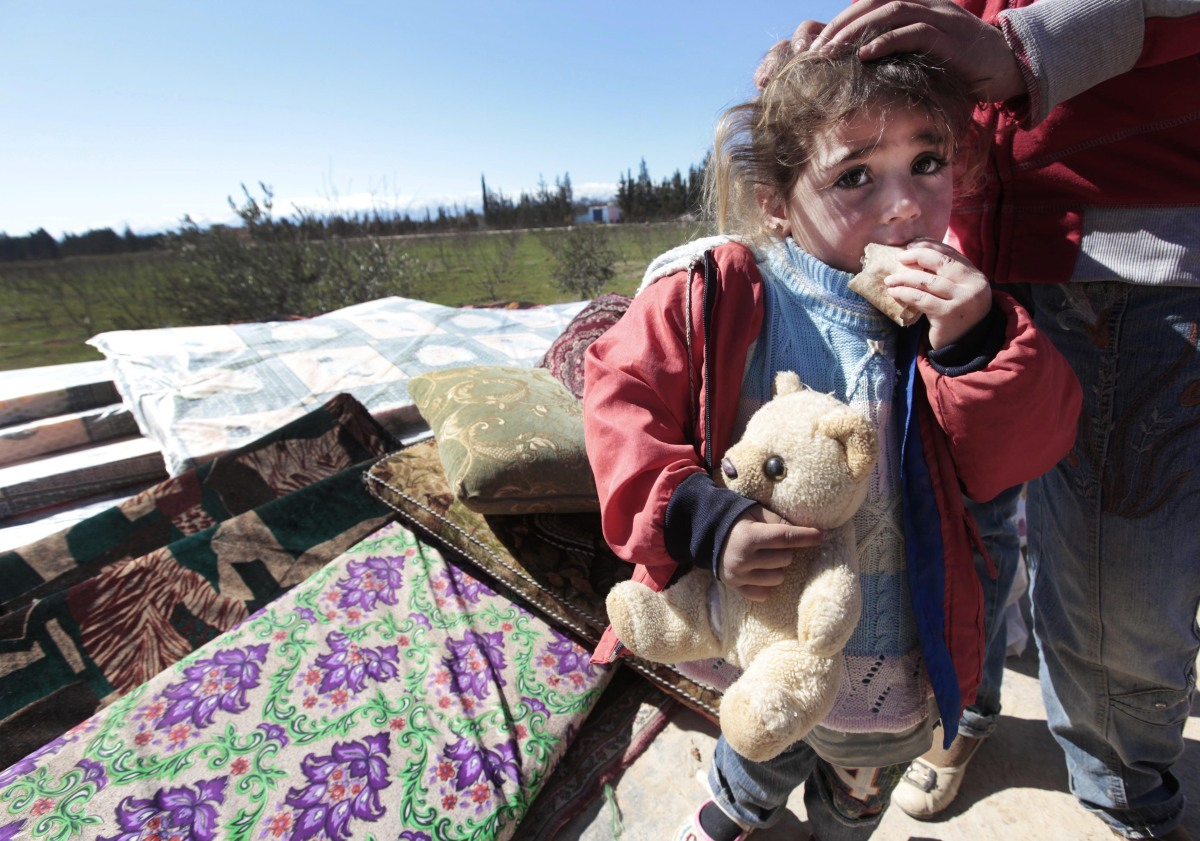 A Syrian child is seen with her family who fled from the Syrian town of Qusair near Homs, at the Lebanese-Syrian border villa