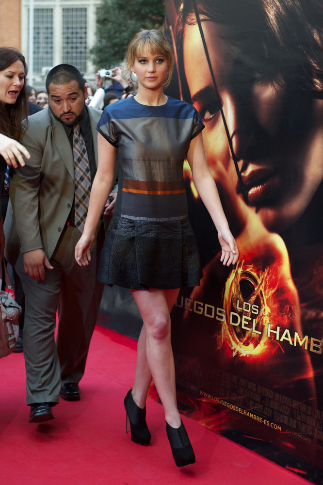 """""""The Hunger Games"""" star pairs her edgy dress with booties for a cool look. The mussed hair keeps the look casual.   Madrid,"""