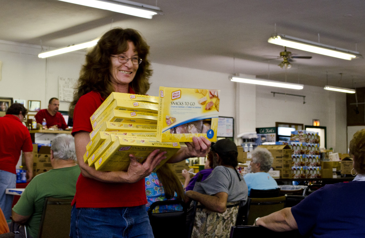 At Colonel Kirk's grocery auction in Millville, Penn., locals gather to bid on outdated and surplus food. A pack of eight por