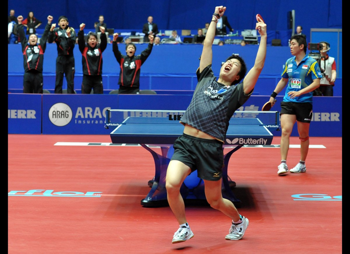 Japan's Jun Mizutani celebrates after defeating the team of Singapore during the quarter finals of the table tennis team Worl