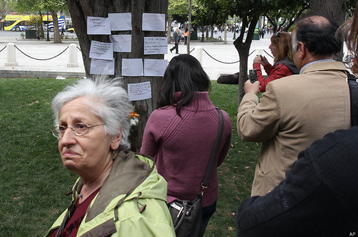 People gather at the site where an elderly man fatally shot himself at Athens' main Syntagma square on Wednesday, April 4, 20