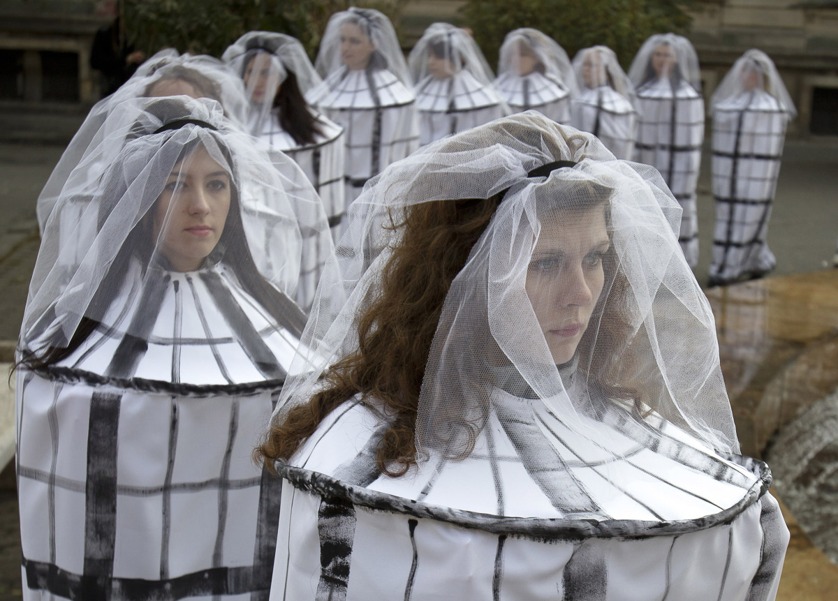 Romanian students dressed as caged brides attend an event to raise awareness to the risks of human trafficking and sexual exp