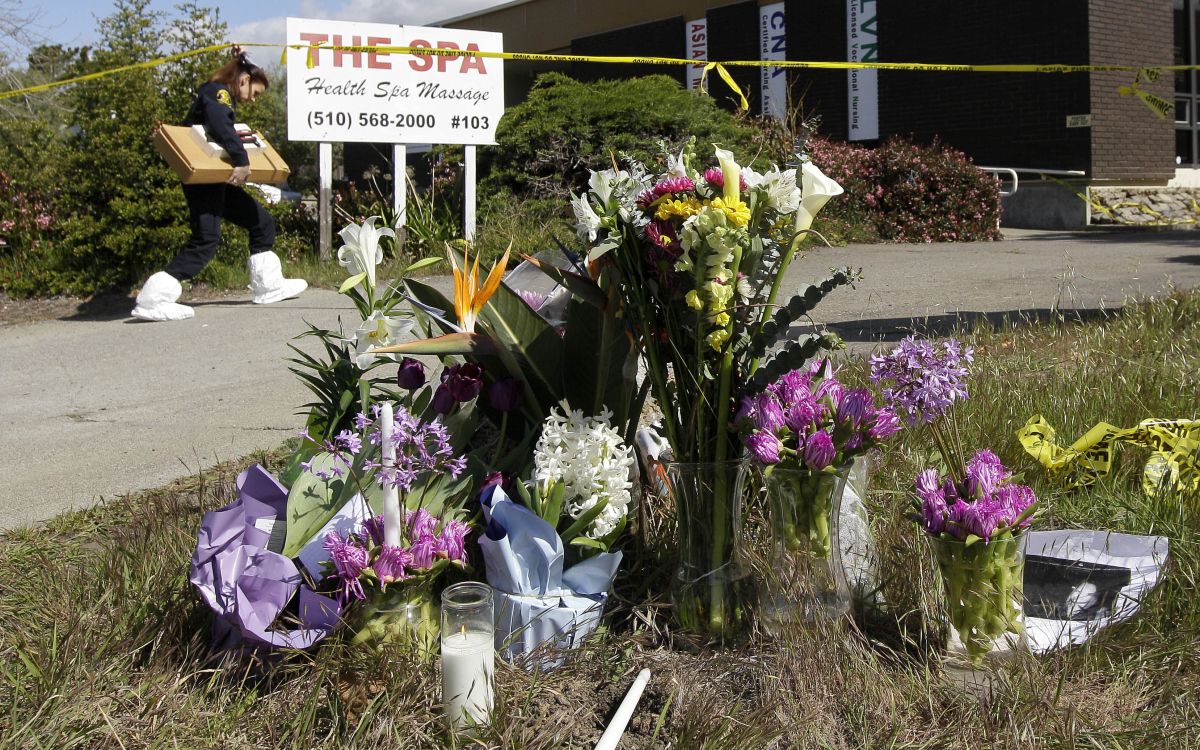 A police investigator walks past flowers left for victims outside of Oikos University in Oakland, Calif., Wednesday, April 4,