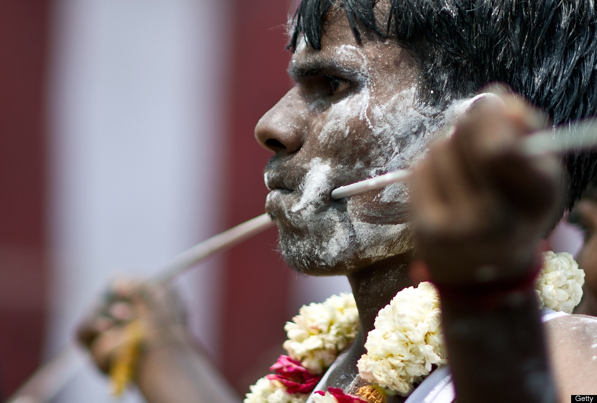An Indian Tamil Hindu devotee with a steel rod pierced through his cheeks takes part in a religious procession for Lord Murug