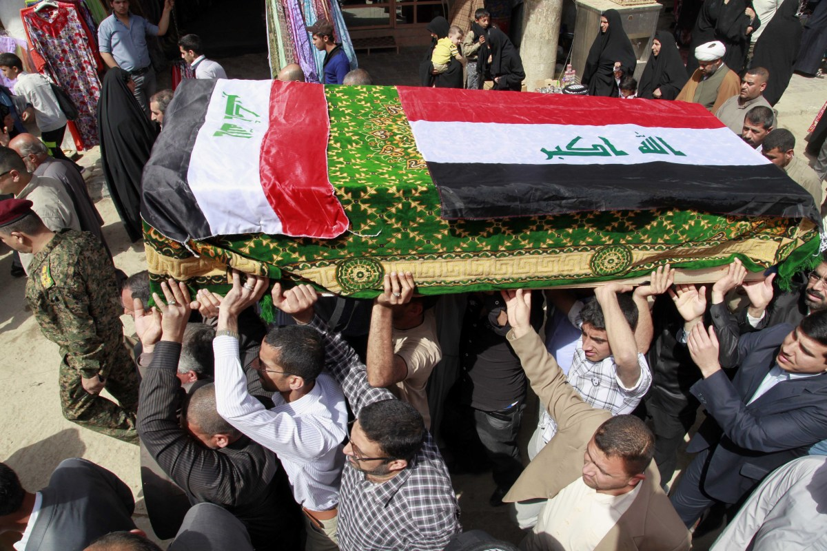 Mourners carry a coffin draped with Iraqi flags during the funeral procession for Shaima Alawadi in the Shiite holy city of N