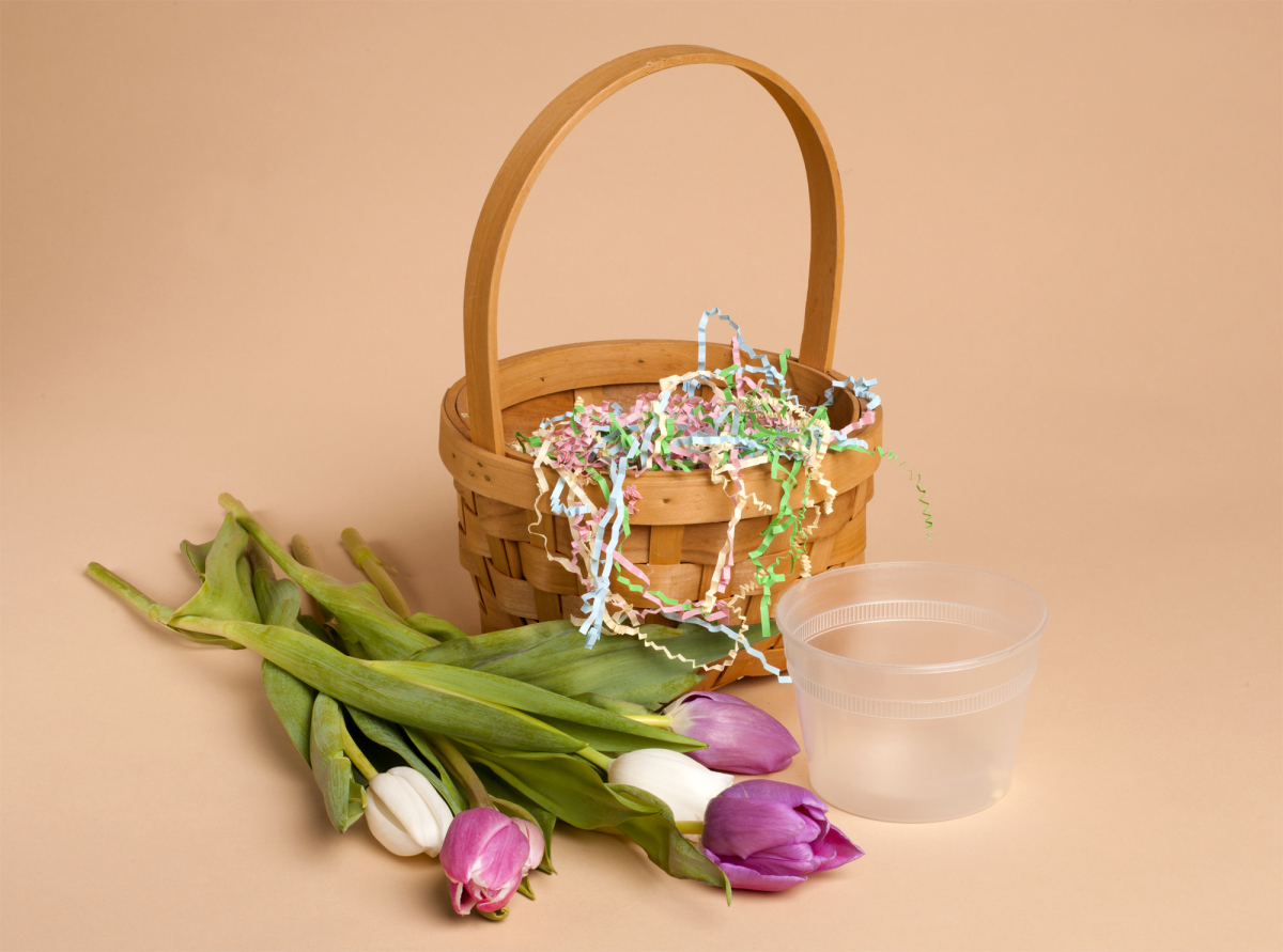 To create this arrangement you will need a basket, a few handfuls of Easter grass (I used the shredded paper variety), an arr