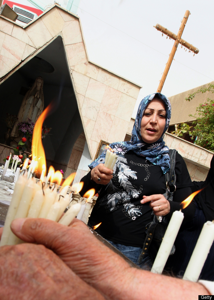 An Iraqi Christian woman lights candles as she attends the Easter Sunday Service at the Virgin Mary Chaldean Christian church