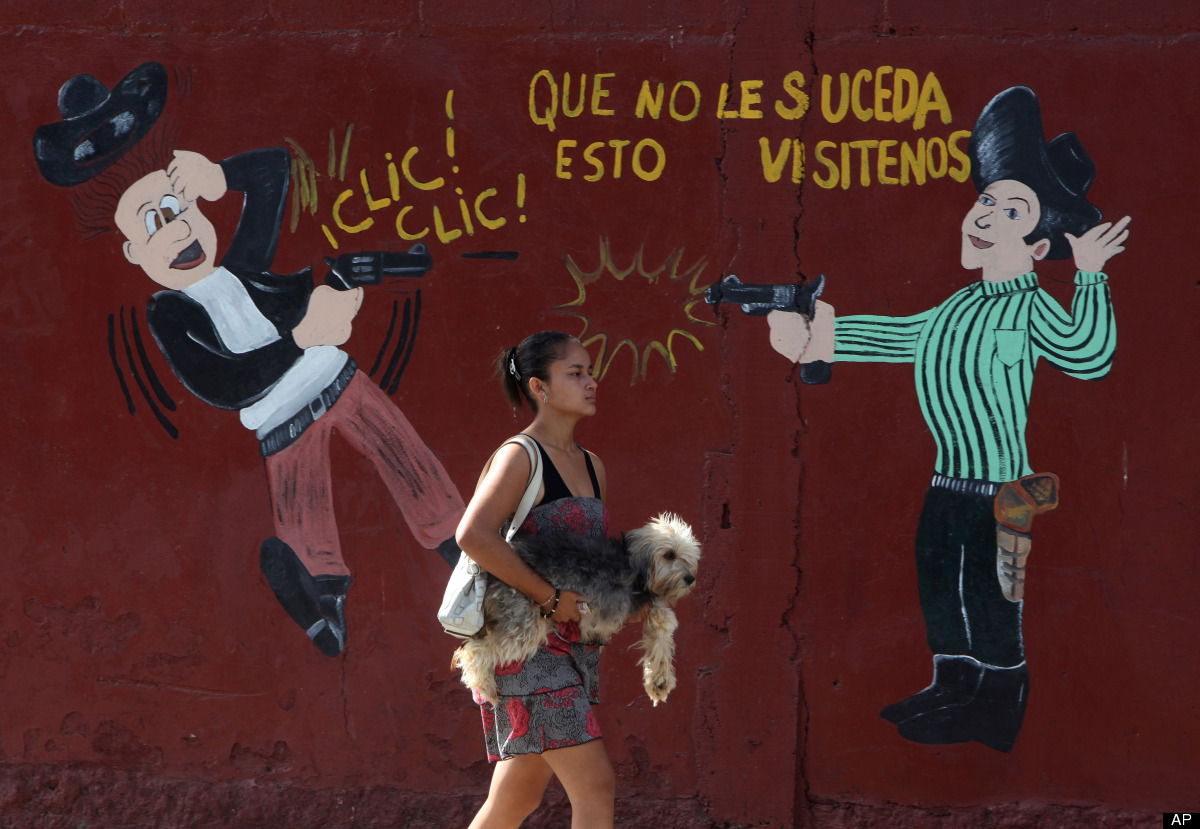 In this March 11, 2012 photo, a woman carries her dog past an armory shop in San Pedro Sula, Honduras. A wave of violence has