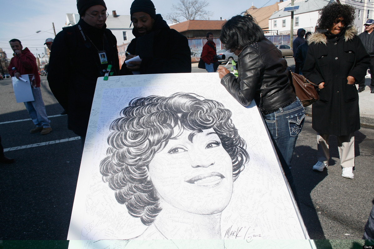NEWARK, NJ - FEBRUARY 18:  Fans sign artwork by artist Mark G at the funeral service for Whitney Houston on February 18, 2012