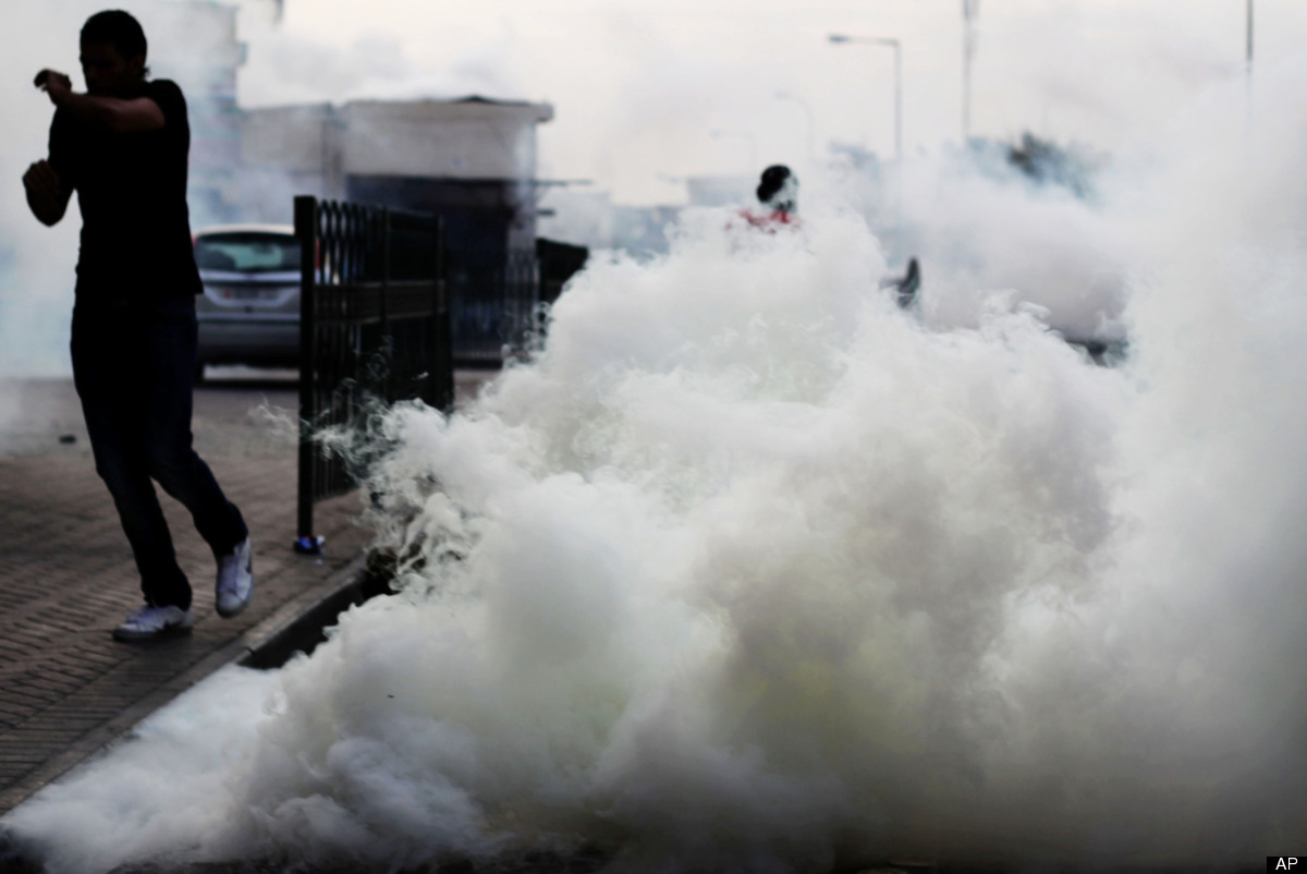 Bahraini anti-government protesters react to tear gas fired by riot police Tuesday, April 10, 2012, in Bilad al-Qadeem, Bahra