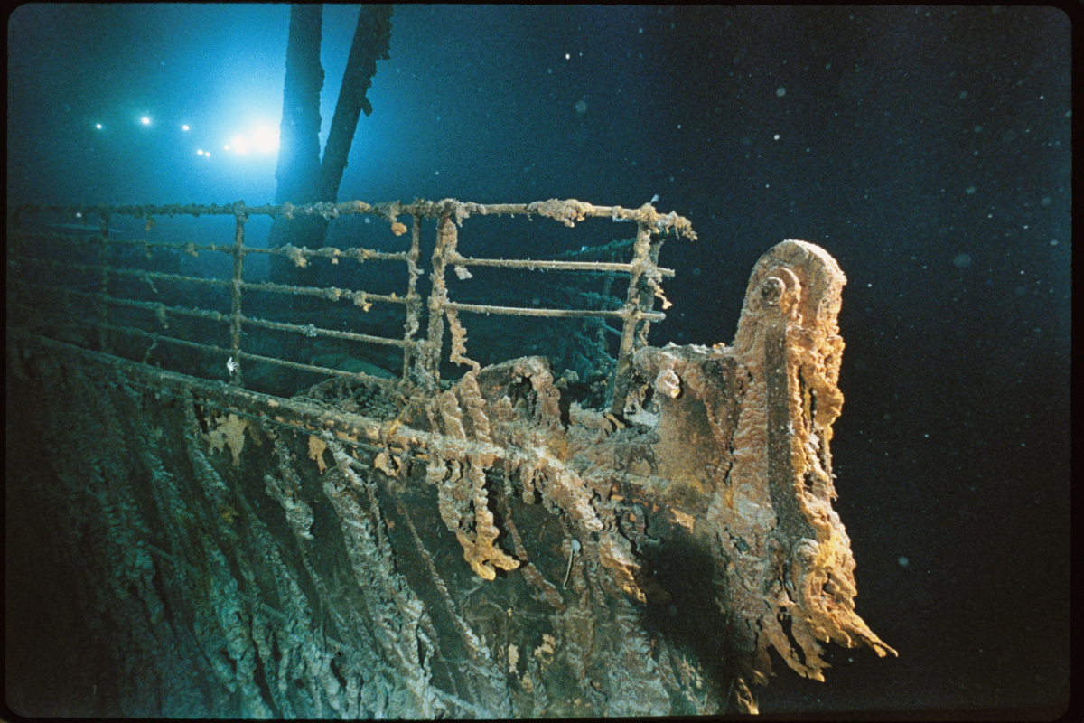 Bow railing of R.M.S. <em>Titanic</em> is illuminated by Mir 1 submersible behind the forward anchor crane.
