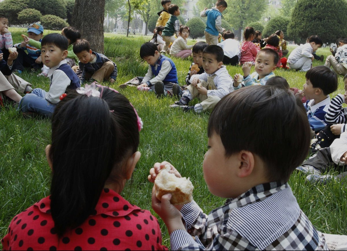 Young North Korean schoolchildren gather together with their teacher during a spring day picnic and a class about the appreci