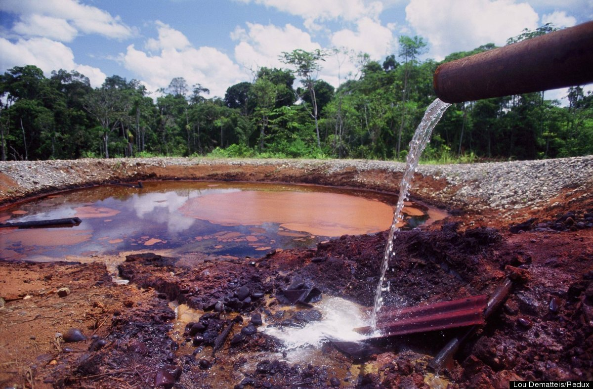 Highly toxic production water pours into a waste pit at an old Texaco oil facility near Dureno in Ecuador's Amazon rainforest