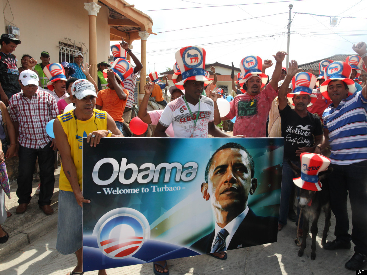 People hold a banner with an image of President Barack Obama during a traditional parade of donkeys in Turbaco, some 20 km so