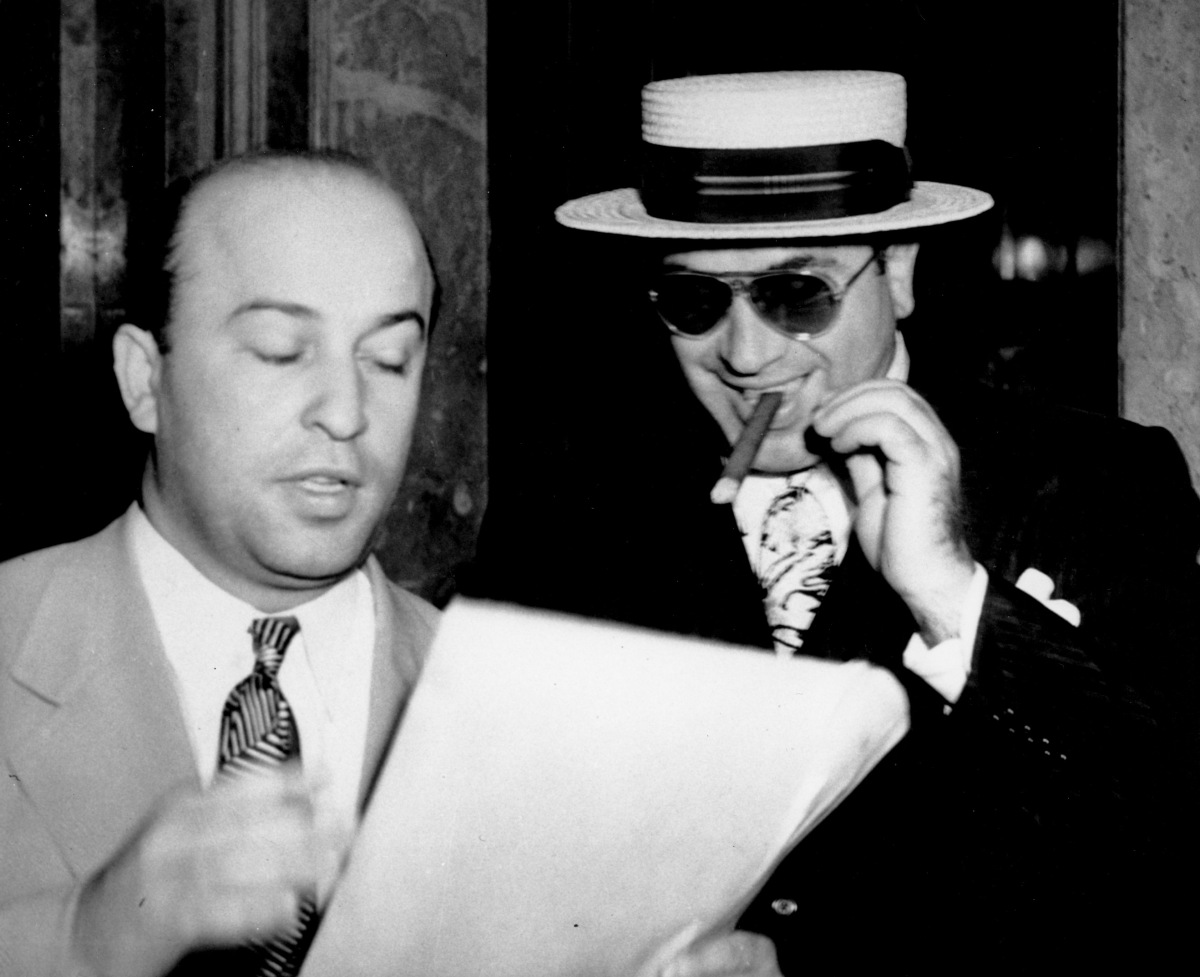 Al Capone, smoking a cigar, listens as his attorney Abe Teitelbaum explains the legal phases of the government's $201,347 tax