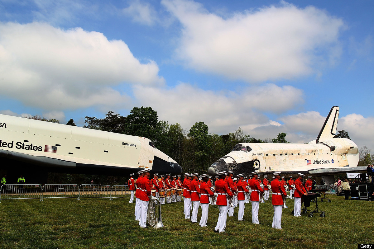 A military band plays as the Space Shuttle Discovery (R), and the Space Shuttle Enterprise, left, sit nose to nose, during an