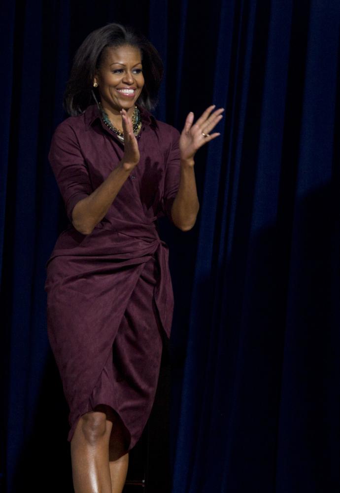 The first lady wore a purplish burgundy dress.