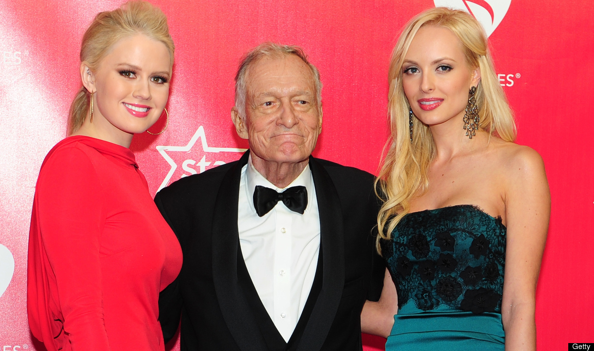 Playboy's Hugh Hefner (C) and his dates pose on arrival for the 2012 MusiCares Person of the Year Tribute honouring Paul McCa
