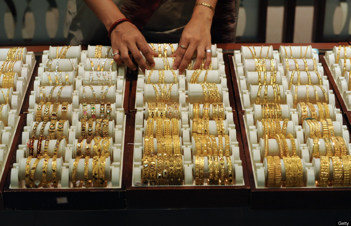 An Indian sales person arranges bangles made of gold and other precious metals on the eve of the Hindu festival, Akshaya Trit