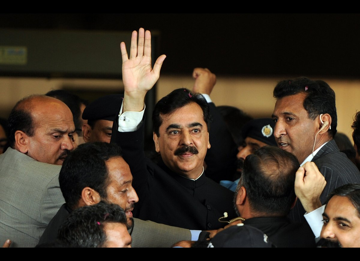 <em>Pakistan's Prime Minister Yousuf Raza Gilani (C) is escorted by security as he waves upon his arrival at the Supreme Cour