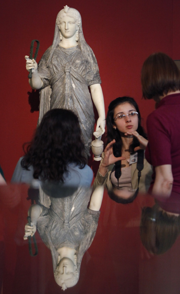 Visitors look at an Isis-Statue, the second century b.c., on display at the exhibition the marking the 100th anniversary of t