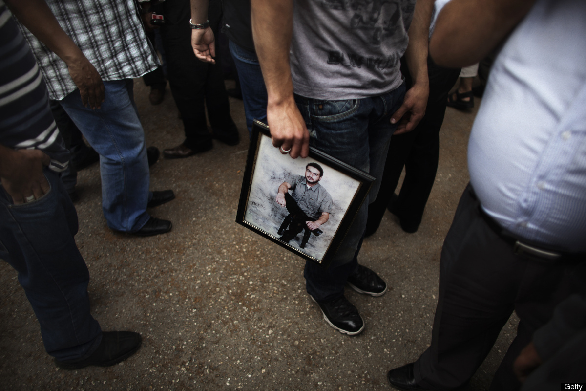 A Palestinian man holds a portrait of a Palestinian prisoner during a protest at International Committee of the Red Cross (IC