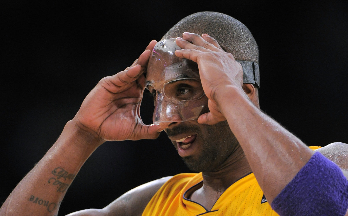 Los Angeles Lakers guard Kobe Bryant adjusts his protective mask during their NBA basketball game against the Minnesota Timbe