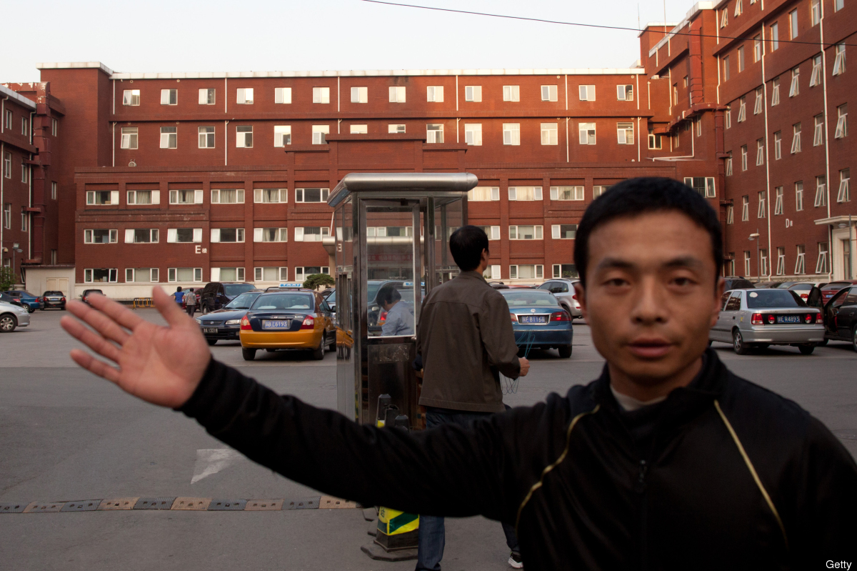 A plainclothes policeman stops the taking of photos outside the Chaoyang Hospital in Beijing where Chinese activist Chen Gua