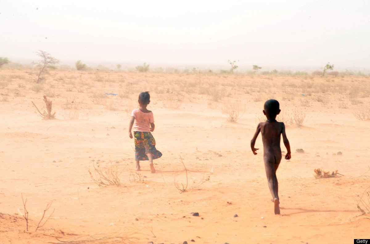 Children of Malian refugees walk bare feet on the burning sand as temperatures are close to 40 Celsius at the Mbere refugee c