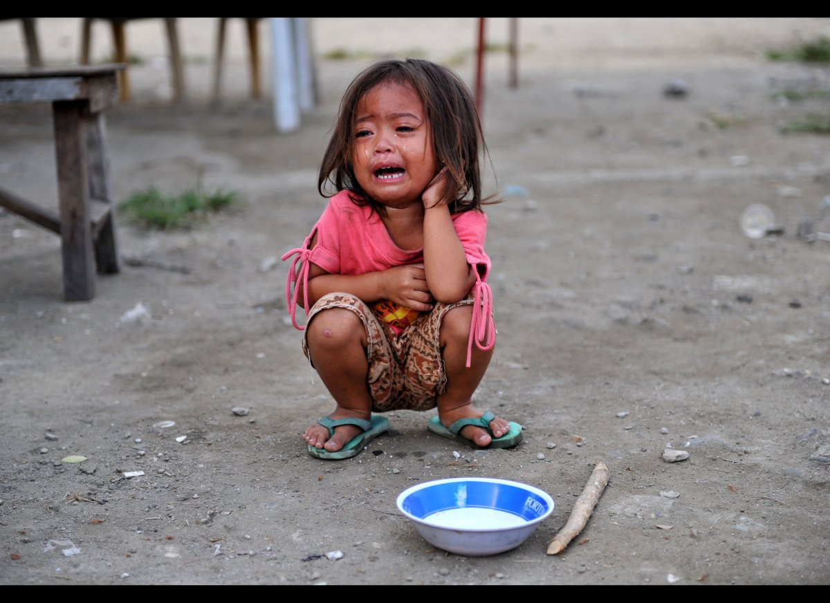 A child cries as she waits to receive rice porridge organized by a child rights group 'Akap Bata' at a slum area in Quezon Ci