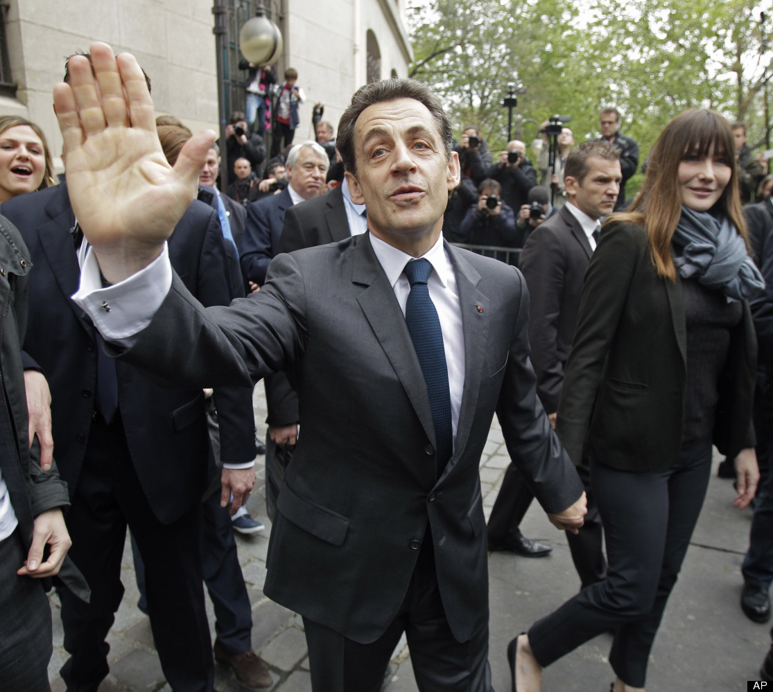 French President and UMP candidate Nicolas Sarkozy waves to wellwishers as he and his wife Carla Bruni-Sarkozy, center right,
