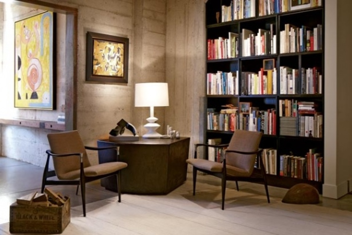 In the living room, gallerist Francis Mill replaced a media center with a floor-to-ceiling bookshelf filled with his favorite
