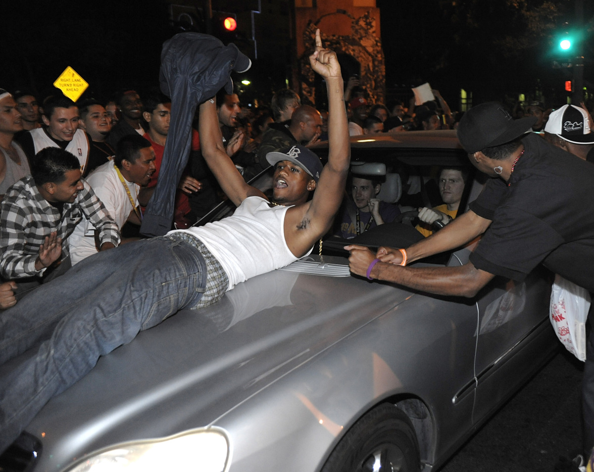 Los Angeles Laker fans celebrate while police try to control a crowd on the street outside the Staples Center in Los Angeles