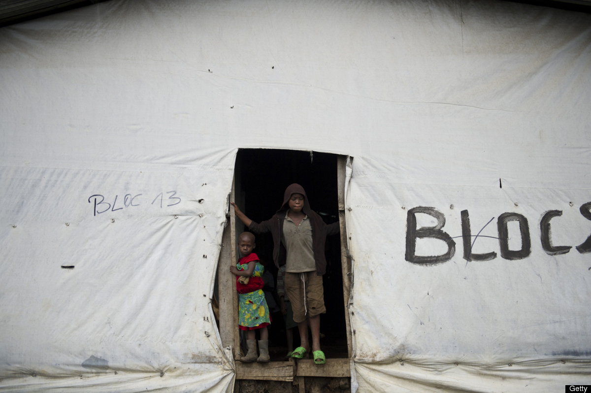 Congolese refugees stand in the entrance to a makeshift shelter in the Nkimira transit camp in western Rwanda on May 5, 2012.