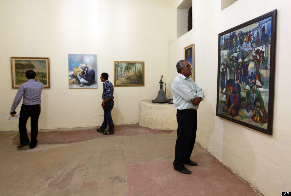 In this Monday, May 7, 2012 photo, visitors look at the paintings during the Babylon Festival of Culture in Hillah, about 60
