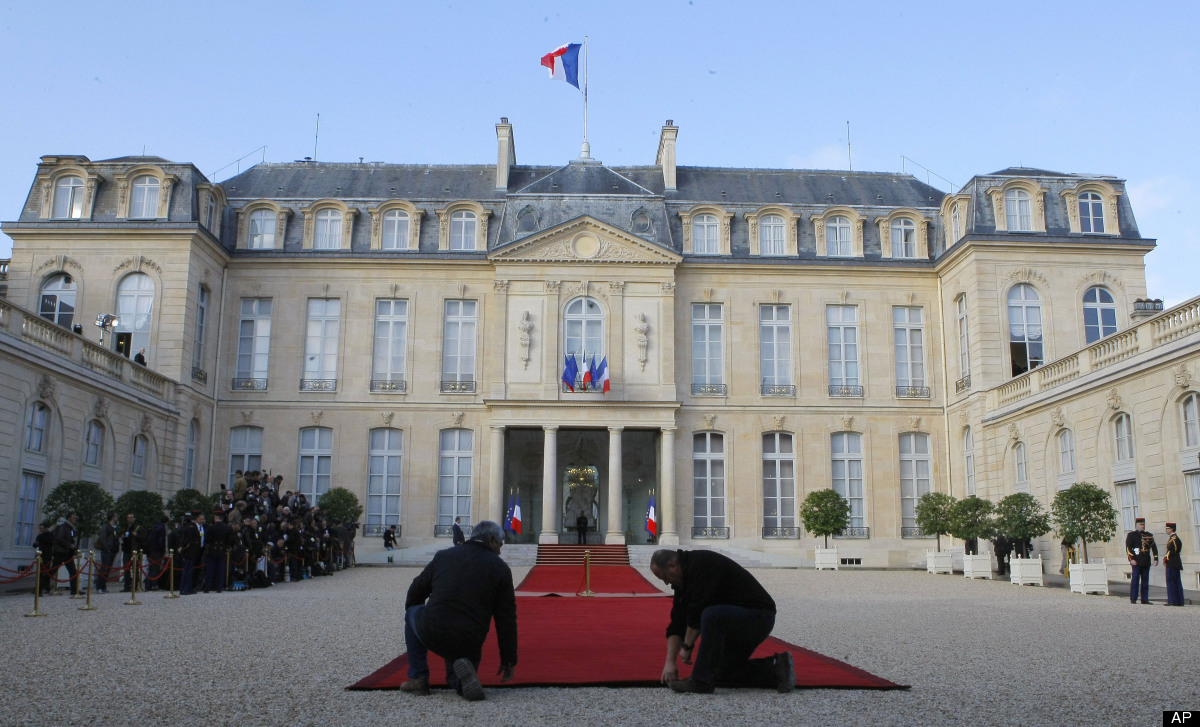 Workers prepare the red carpet for the takeover ceremony between outgoing President Nicolas Sarkozy and President-elect Franc